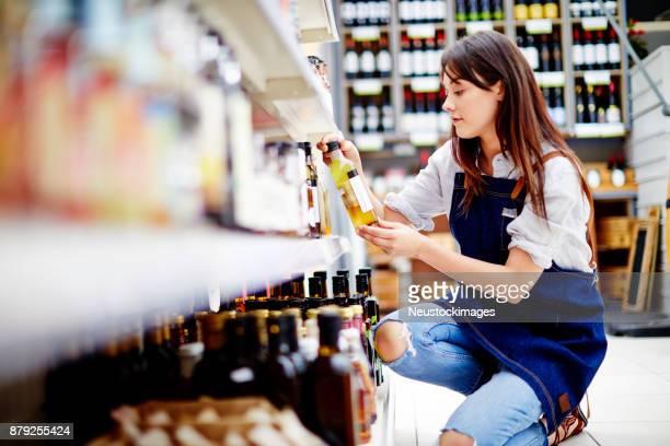 若い女性デリ オーナー店でサラダのドレッシングのボトルを調べる