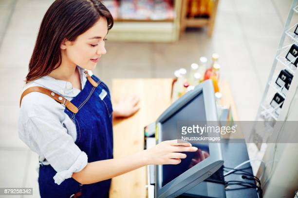 Young female deli owner using cash register in store