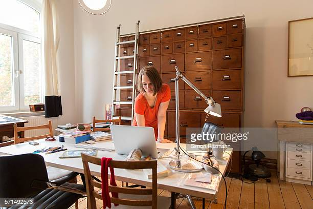 Young female designer working in home office