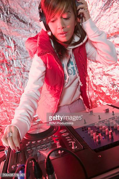 young female dj at work, adjusting controls, one hand to headphones - clubkleding stockfoto's en -beelden