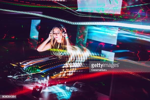 young female dj mixing music in a nightclub - electronic music stock pictures, royalty-free photos & images
