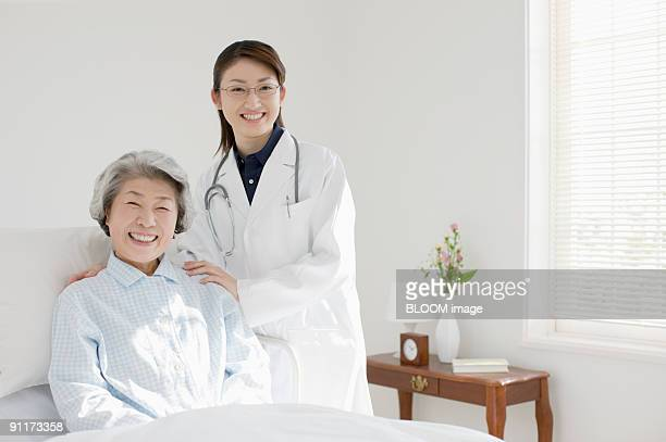 Young female doctor and senior female patient, smiling, portrait