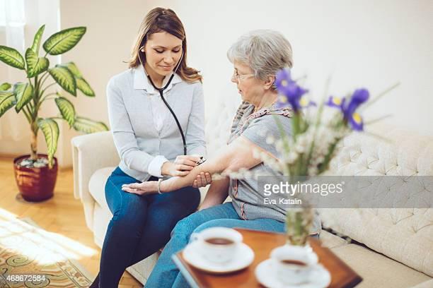Jovem mulher médico examina os doentes idosos