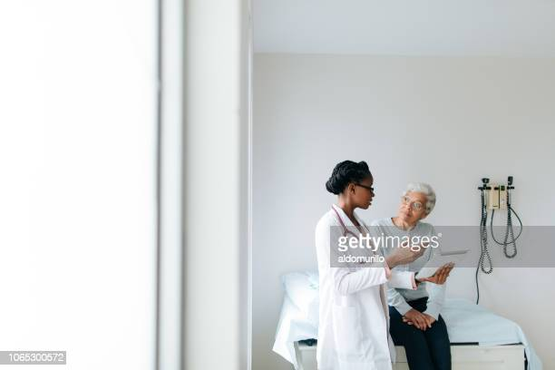 young female doctor explaining patient with digital tablet - doctor and patient stock pictures, royalty-free photos & images