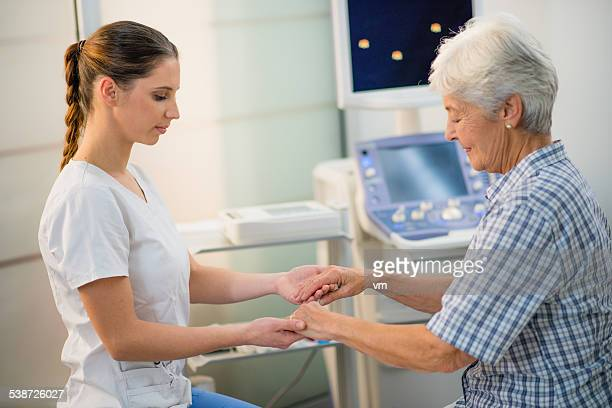 Young Female Doctor Holding a Senior Woman's Hands