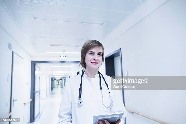 young female doctor holding clipboard in hospital corridor, freiburg im breisgau, baden-württemberg, germany - sigrid gombert stock pictures, royalty-free photos & images
