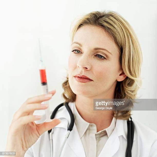 Young female doctor holding up a full syringe