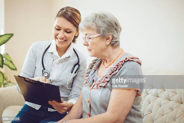 Young female doctor is consulting a senior patient