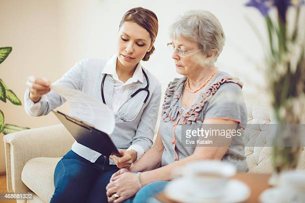 young female doctor is consulting a senior patient - carers stock photos and pictures