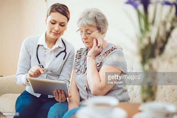 Jovem mulher médico consulta um doente idoso