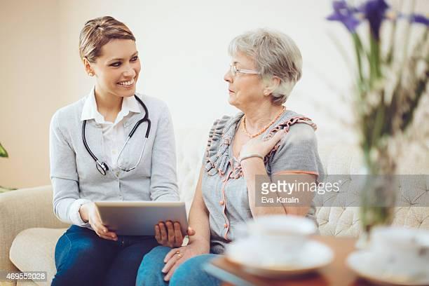 Junge weiblich Arzt Beratung eine senior Patienten