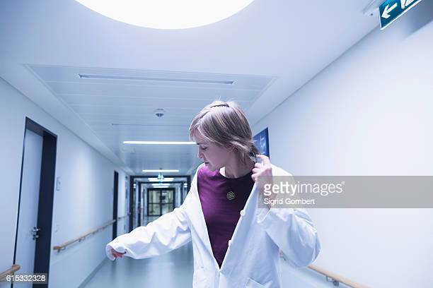 young female doctor looking at her hand while walking in hospital corridor, freiburg im breisgau, baden-württemberg, germany - sigrid gombert imagens e fotografias de stock