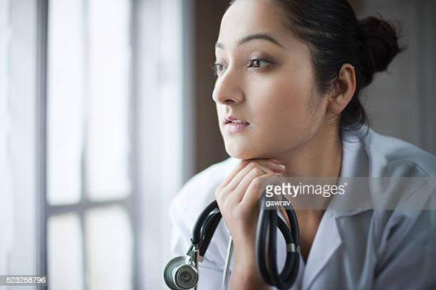 Young female doctor looking at view near window and thinking.
