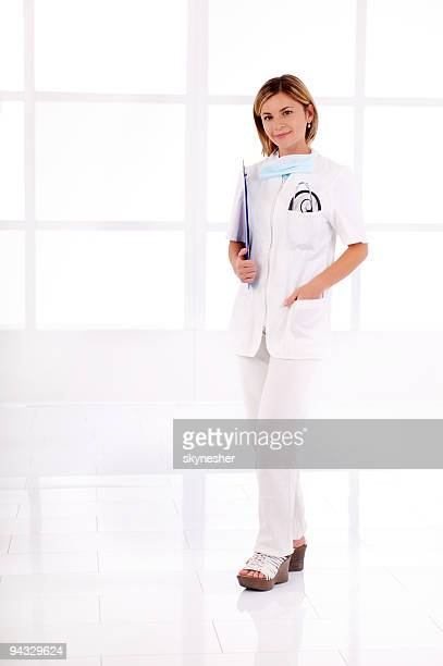 Young female doctor standing in the hall.