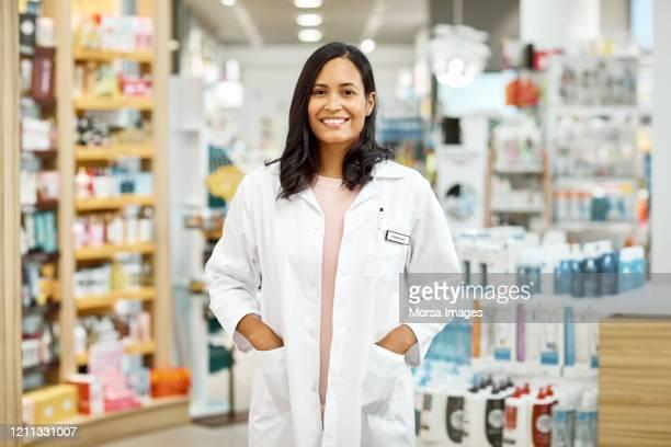 young female doctor standing with hands in pockets - medicamento fotografías e imágenes de stock