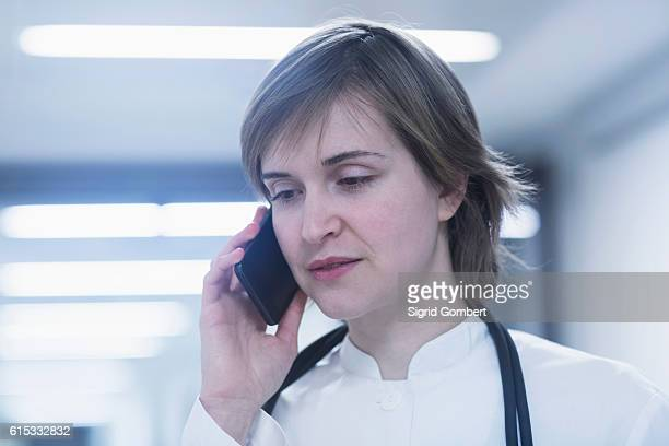 young female doctor talking on mobile phone in hospital corridor, freiburg im breisgau, baden-württemberg, germany - sigrid gombert stock pictures, royalty-free photos & images