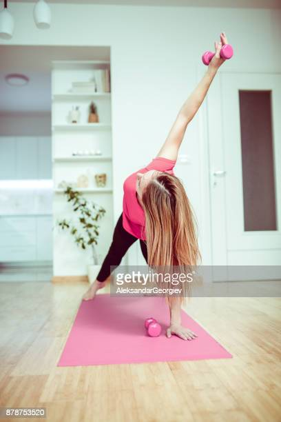 young female doing pust ups with weights at home in the morning - aleksandar georgiev stock photos and pictures