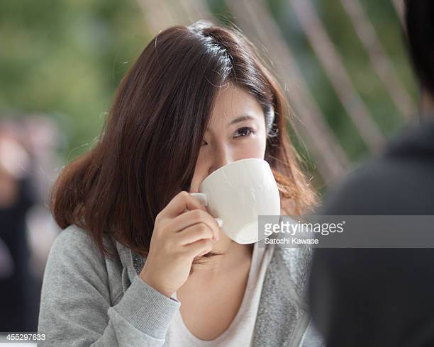 Young female drining a cup of coffe at a terrace