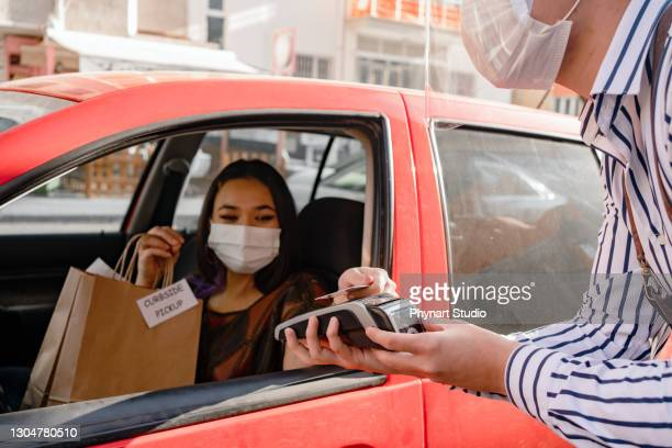 young female driver receiving a packed coffee from a coffee shop - flatten the curve stock pictures, royalty-free photos & images