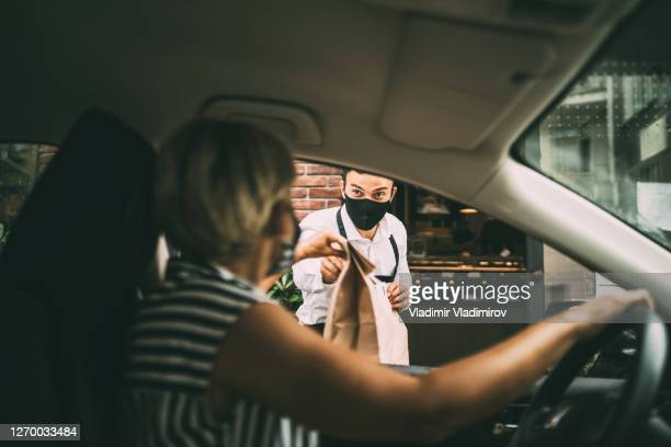 young female driver recieving a packed food from a restaurant - curbside pickup stock pictures, royalty-free photos & images
