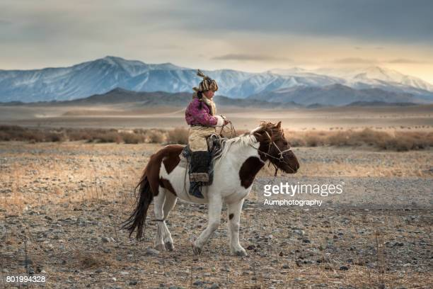 young female eagle hunter riding horse through field at the altai moutains, mongolia. - mongolian women stock photos and pictures