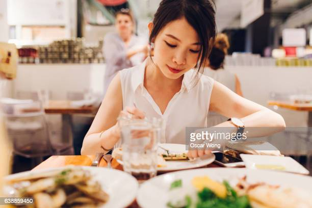 Young female eating in an Italian restaurant with friend