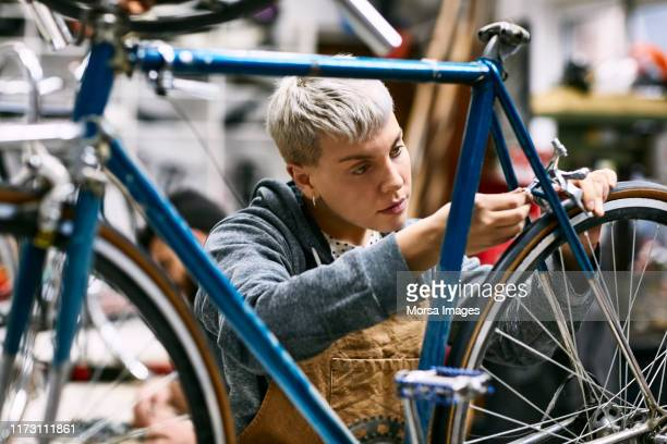 young female employee repairing bicycle brake - repair shop stock pictures, royalty-free photos & images