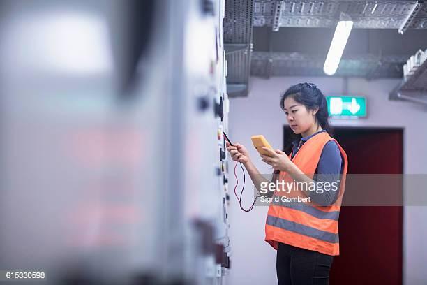 young female engineer examining control panel with multimeter in an industrial plant, freiburg im breisgau, baden-württemberg, germany - sigrid gombert stock-fotos und bilder