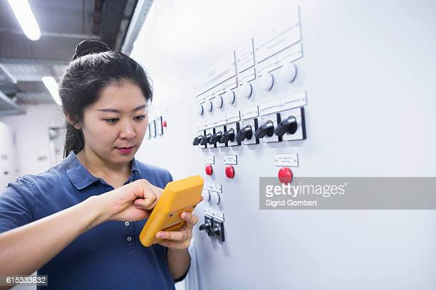 young female engineer examining control panel with multimeter in an industrial plant, freiburg im breisgau, baden-württemberg, germany - sigrid gombert stock-fotos und bilder