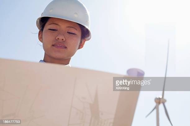 Young female engineer holding open and looking down at blueprints, on site with wind turbines