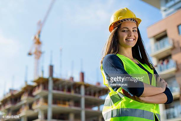 young female engineer smiling at construction site - proteção - fotografias e filmes do acervo