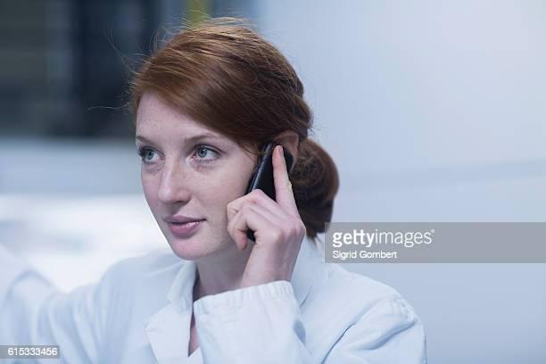 young female engineer talking on a mobile phone near switchgear in an industrial plant, freiburg im breisgau, baden-württemberg, germany - sigrid gombert stock-fotos und bilder