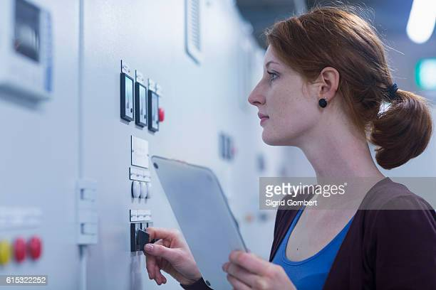 Young female engineer updating control panel using digital tablet in an industrial plant, Freiburg im Breisgau, Baden-Württemberg, Germany