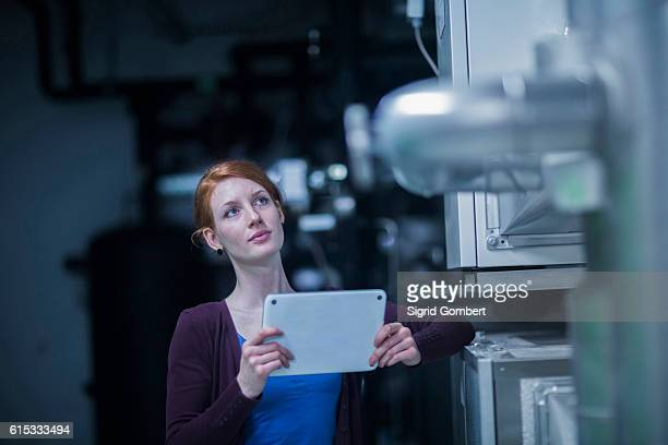 young female engineer using a digital tablet and thinking in an industrial plant, freiburg im breisgau, baden-württemberg, germany - sigrid gombert stock-fotos und bilder