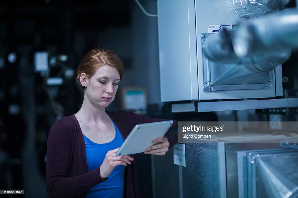 Young female engineer using a digital tablet in an industrial plant, Freiburg im Breisgau, Baden-Württemberg, Germany : Stock-Foto