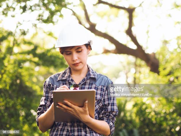 Young Female Engineer Using Digital Tablet Against Trees