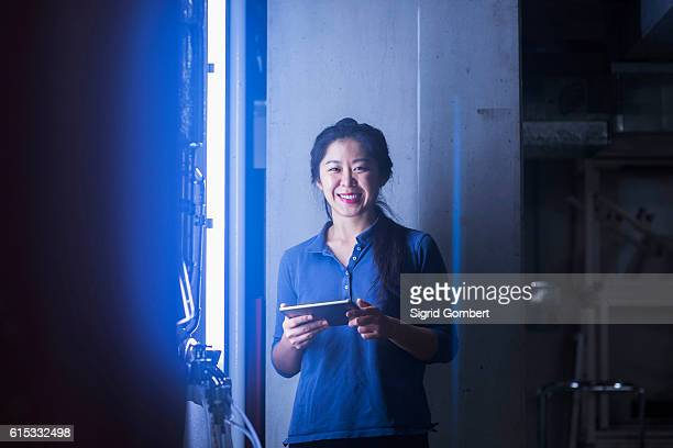 Young female engineer using digital tablet and smiling in an industrial plant, Freiburg im Breisgau, Baden-Württemberg, Germany