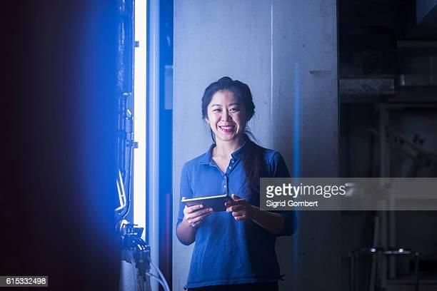 young female engineer using digital tablet and smiling in an industrial plant, freiburg im breisgau, baden-württemberg, germany - sigrid gombert stock-fotos und bilder
