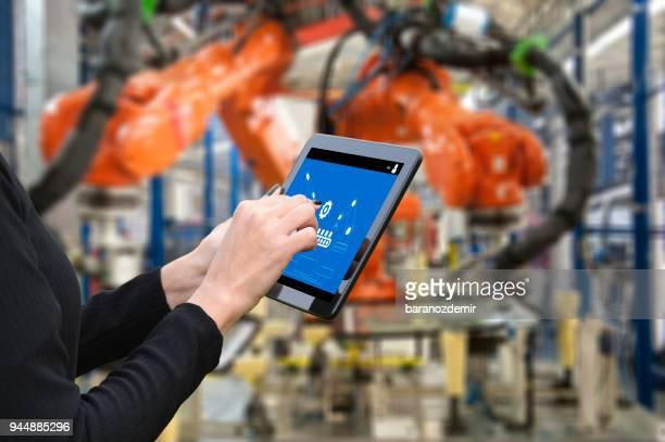 jovem engenheiro feminino usando tablet digital para operar o braço robótico - robô - fotografias e filmes do acervo