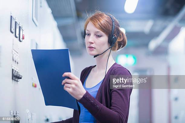 Young female engineer wearing headset and controlling a switch gear in control room, Freiburg im Breisgau, Baden-Württemberg, Germany