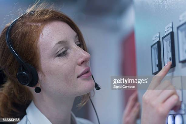 young female engineer wearing headset and examining in control room, freiburg im breisgau, baden-württemberg, germany - sigrid gombert stock-fotos und bilder