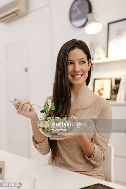 Young female entrepreneur eating salad at lunch
