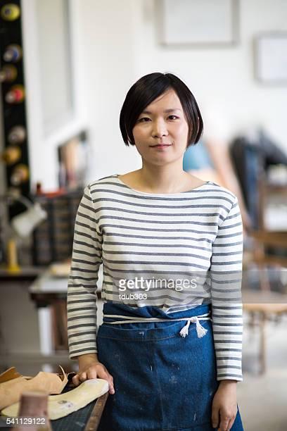 若い女性は彼女の靴作りアントレプレナースタジオ