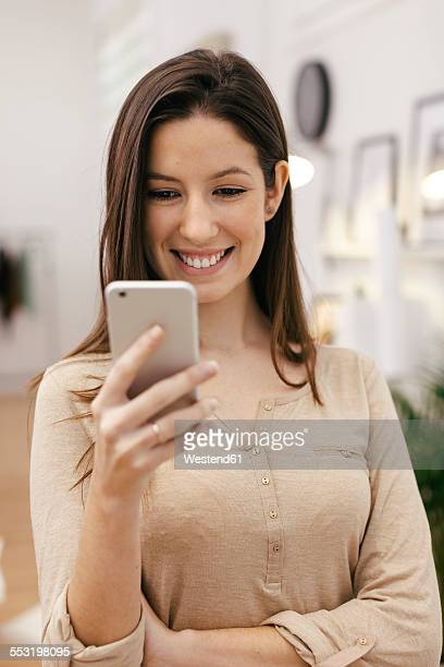 Young female entrepreneur using smartphone at home office
