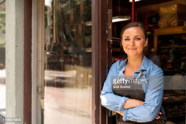 jonge vrouwelijke ondernemer werkzaam bij haar kleine workshop business - onafhankelijkheid stockfoto's en -beelden