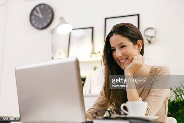 Young female entrepreneur working with laptop at home office