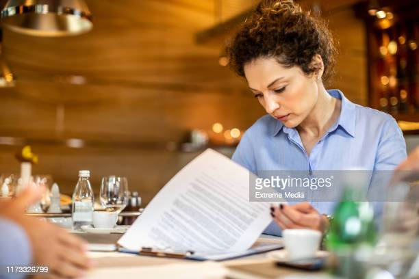 young female entrepreneur writing on a paper document in a restaurant - financial analyst stock pictures, royalty-free photos & images