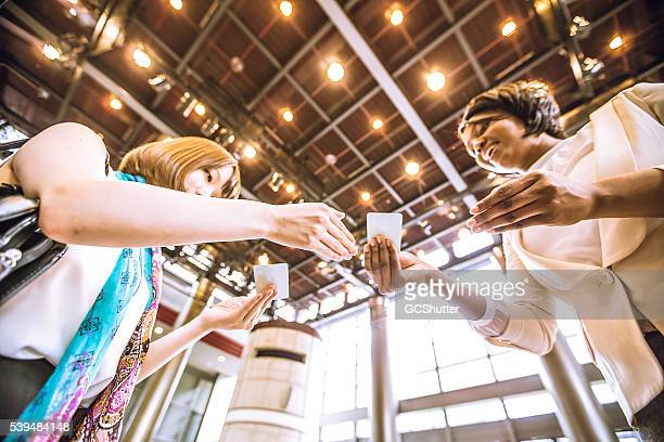 Business card stock photos and pictures getty images young female entrepreneurs exchanging business cards reheart Choice Image