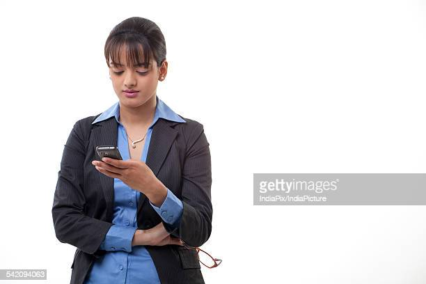 Young female executive reading text message over white background