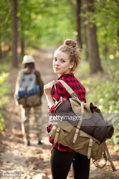 young female explorer hiking with friend in forest - izusek stock pictures, royalty-free photos & images